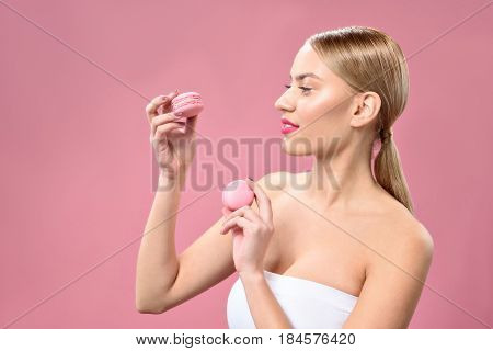 Sweet treats. Waist up portrait of smiling blonde girl holding pink macaroons with copy space in left side