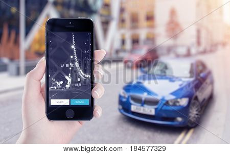 Varna Bulgaria - May 25 2015: Uber application startup page on the Apple iPhone 5S display in female hand. Blurred street view with car and flare sun light on the background.