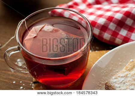 Cup Of Red Fruit Tea With Teabag In It On A Wooden Table