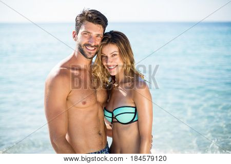 Portrait of happy young couple standing with arm around on shore at beach