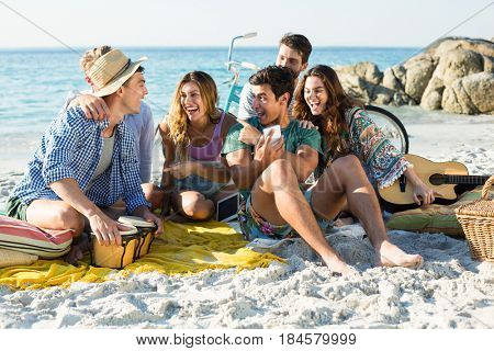 Friends laughing while sitting on shore at beach