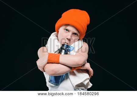 Boy In Hat With Towel On Neck Hugging Bottle And Drinking Water Isolated On Black