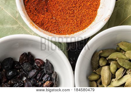 Paprika Powder, Barberry And Cardamon Seeds In White Ceramic Bowls, Top View, Closeup Shot
