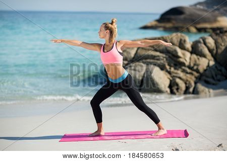 Full length of young woman practicing warrior pose at beach