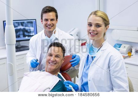 Portrait of smiling dentists and male patient in clinic