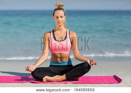 Full length of young woman meditating in lotus position on shore at beach