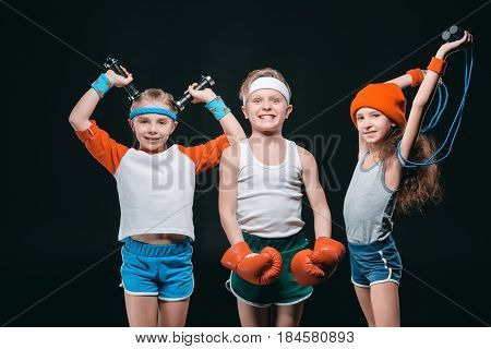 Three Smiling Kids In Sportswear Posing With Sport Equipment And Looking At Camera