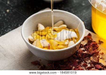 Honey Trickle In Bowl Full Of Peeled Peanuts In It On A Wooden Table