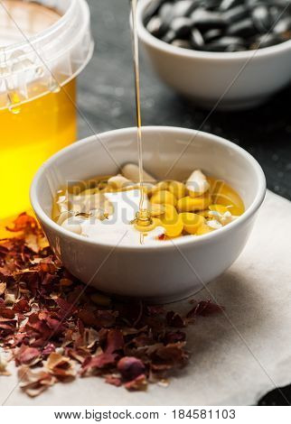 Thin Honey Trickle Poured In White Bowl Full Of Raw Peanuts, Vertical
