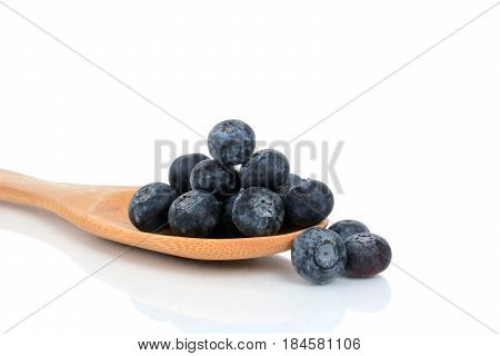 fresh blueberries on wooden spoon white background