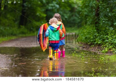 Kids Playing In The Rain With Umbrella