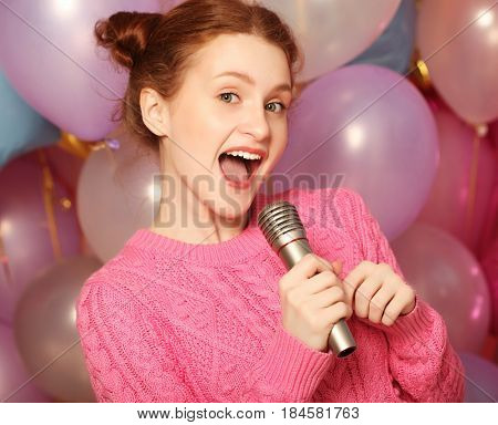 Happy singing girl. Beauty woman with microphone over  backgroun