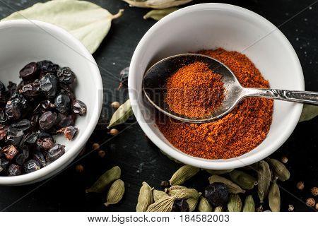 Paprika Powder In A White Ceramic Bowl With Metal Spoon, Top View, Selective Focus