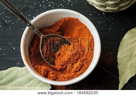 Ground Paprika Powder In A White Ceramic Bowl With Metal Spoon In It On A Black Wooden Table, Top Vi