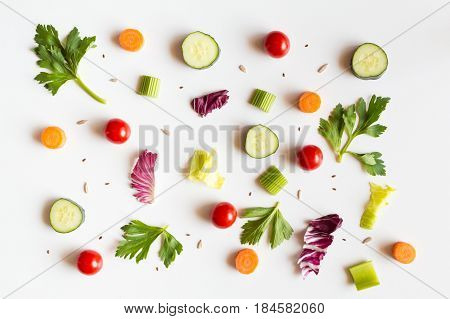 Eating pattern with raw ingredients of salad, lettuce leaves, cucumbers, red tomatoes, carrots, celery and seeds on white background