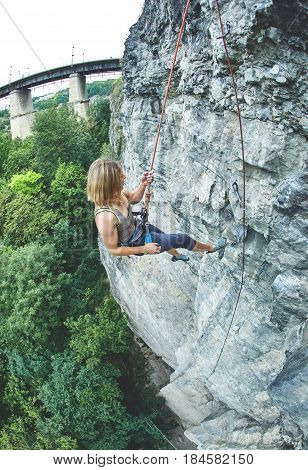 woman rock climber climbs on the cliff. rock climber climbs on a rocky wall. woman descends on a rope down.