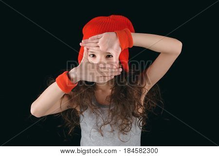 Girl In Sportive Clothingobscuring Face With Hands Isolated On Black