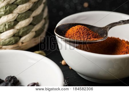 Ceramic Bowl With Ground Paprika And Metal Spoon Above It