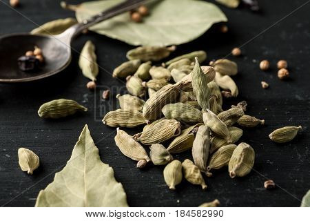 Cardamon Dry Seeds And Laurel Leafs On A Black Wooden Table, Closeup Shot