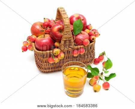 apples in a wicker basket and a glass of juice isolated on white background. horizontal photo.