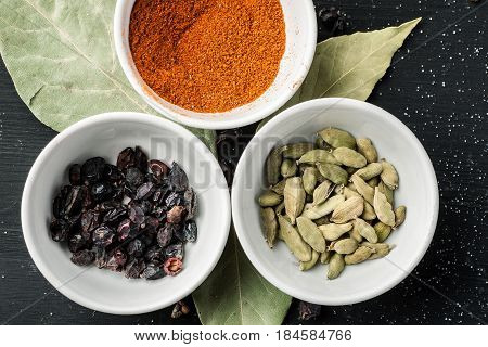 Paprika Powder, Barberry And Cardamon Seeds In White Ceramic Bowls On A Black Wooden Table, Top View