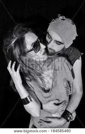 Stylish young man and woman embracing. Fashion studio photo
