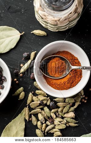 Paprika Powder In A White Ceramic Bowl With Metal Spoon, Top View, Selective Focus, Vertical