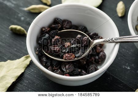 Barberry Berries In White Ceramic Bowl With Metal Spoon In It On A Black Wooden Table