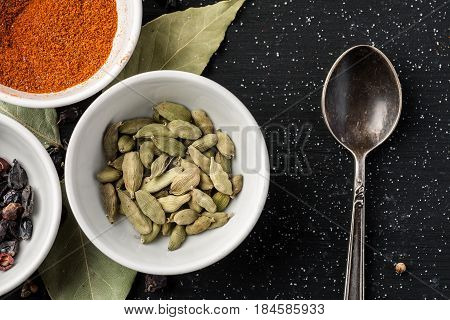 Condiments In A White Ceramic Bowls On A Black Wooden Table With Metal Spoon On It, Top View