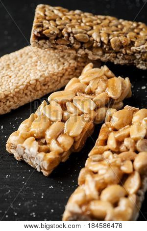 Peanut, Sesame And Sunflower Seed Brittle On A Black Wooden Table, Vertical