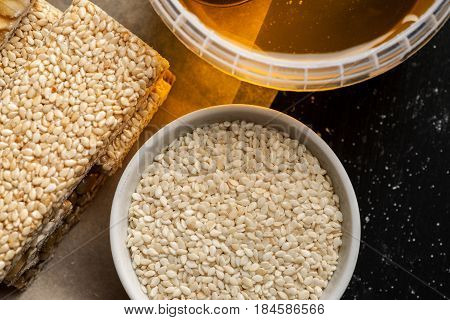 Honey Jar, Sesame Seeds In A White Bowl And Few Brittle On A Wooden Table, Top View