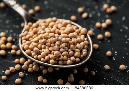 White Mustard Seeds In Metal Spoon On A Black Wooden Table, Selective Focus