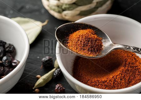 Paprika Powder In A White Ceramic Bowl With Metal Spoon, Selective Focus