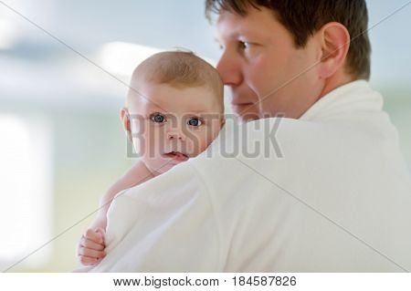 Young father and his little cute newborn baby daughter together in spa hotel. Dad in white bathrobe holding child, adorable girl on arms. Family relaxing in indoors swimming pool with baby massage