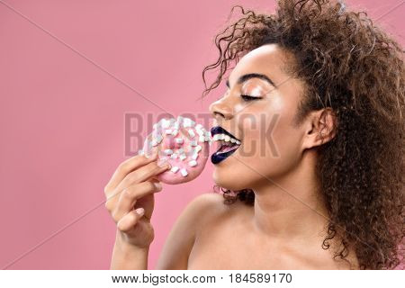 Side view of smiling young african woman eating delicious donut with marshmallows with pink copy space in left side
