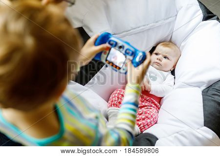 Two siblings kids boys taking picture with toy camera of cute baby girl. Brothers and little tiny sister having fun together. Memories for family album. Three children playing.