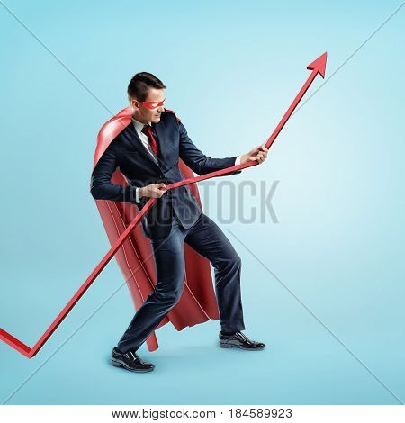 A businessman wearing a red superhero cape trying to hold a red statistic arrow with force on blue background. Working hard. Business results. Personal effort.