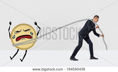A businessman pulling away an unwilling and crying large golden coin with a rope. Keep budget under control. Savings and loans. Wise spending.