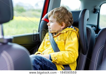 Adorable cute preschool kid boy sitting in car in yellow rain coat. Little school child in safety car seat with belt enjoying trip and jorney. Safe travel with kids and traffic laws concept.