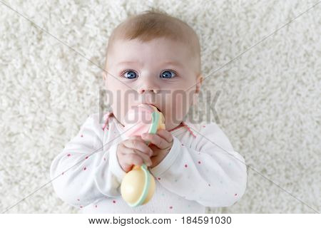 Cute adorable newborn baby playing with colorful pastel vintage rattle toy. New born child, little girl looking at the camera. Family, new life, childhood, beginning concept. Baby learning grab