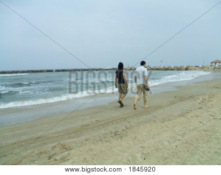 Couple/ Friends Walking On The Beach