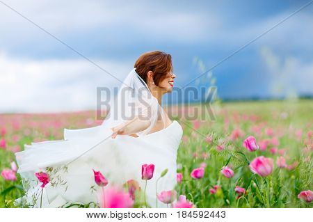Beautiful happy bride in white dress  having fun in flower poppy field on summer day. Just married, young amazing woman.