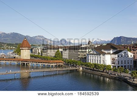 Lucerne Switzerland - May 06 2016: Aerial view towards landmarks by the river Reuss. The Chapel Bridge connects the two banks of the river and octagonal tower can be seen there