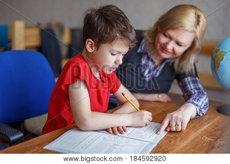 Mother helps to son solve math homework at desk
