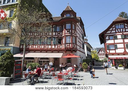 Lucerne Switzerland - May 06 2016: Half-timbered houses adorns cityscape. In one of them on the ground floor is outdoor seating restaurant in front of which people spend a nice time
