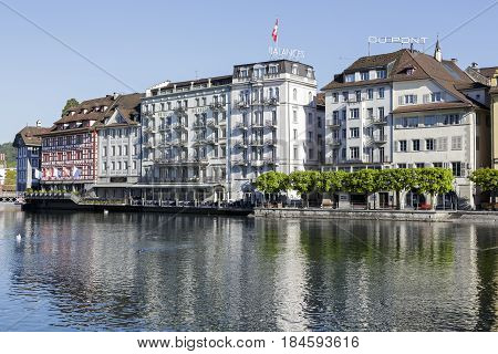 Lucerne Switzerland - May 05 2016: Historical townhouses along the waterfront by river Reuss. There are trees that grow along the promenade next to the river
