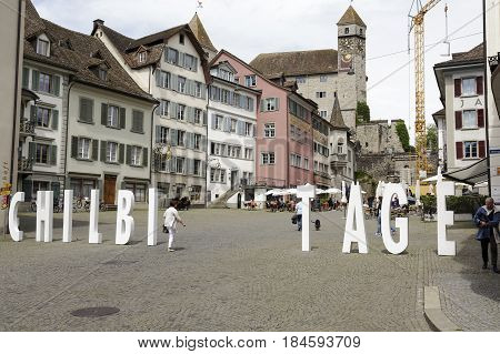 Rapperswil Switzerland - May 10 2016: Buildings in the old town and on the way that leads to a castle a large white lettering was set. Several people can be seen in a distance
