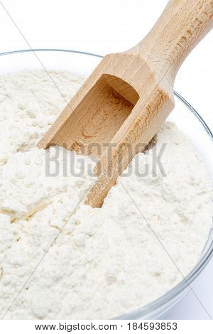 Glass bowl of wheat flour isolated on white