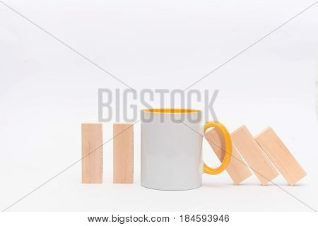 A cup of tea or coffee stop the Domino principle. Business concept. On a white background. Horizontally.