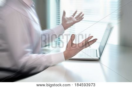 Confused and stressed businessman spreading hands in office and don't know what to do. Problem with failing business or confusion with crisis. Laptop broken or internet connection not working.